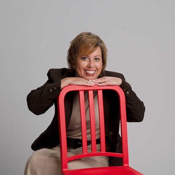 Woman sitting behind the iconic red chair smiling.