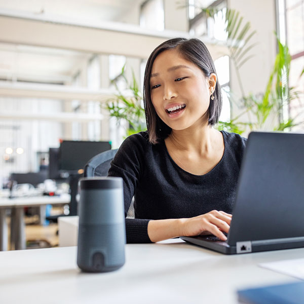 Asian businesswoman talking to virtual assistant at her desk. Female professional working on laptop and talking into a speaker.